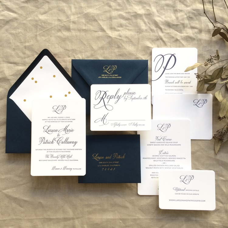 Larson by BTElements, Formal but festive wedding invitation with calligraphy style script, gold foil and navy letterpress, navy envelopes and gold confetti envelope liner, monogram on wedding invitation and rounded corners, reply set, menu and thank you note also shown on white paper with navy ink