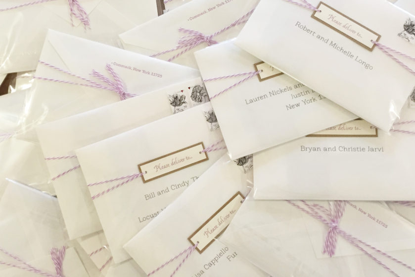 Whimsical Wedding Invitations, stack of mailing envelopes, floral stamps and lilac bakers twine details