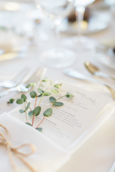 Rustic wedding menu, tucked into a napkin with greenery embellishments