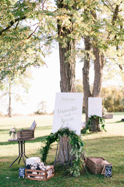 Welcome Sign with greenery draped over the easel, outdoor wedding on a sunny day
