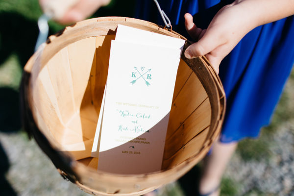 Rustic Ceremony Programs, Trifold program with arrow and heart monogram detail, green inks on natural speckled paper, sitting in apple basket