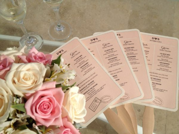 Fan Programs for Destination Weddings, blush and gray inks on textured white paper, sitting next to pink bouquet