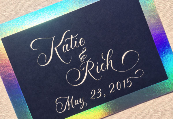 White calligraphy of names and wedding date on black paper with colorful hologram border