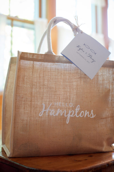 Hospitality Bag for a hamptons wedding, burlap bag with white text, blue itinerary booklet attached to the handle