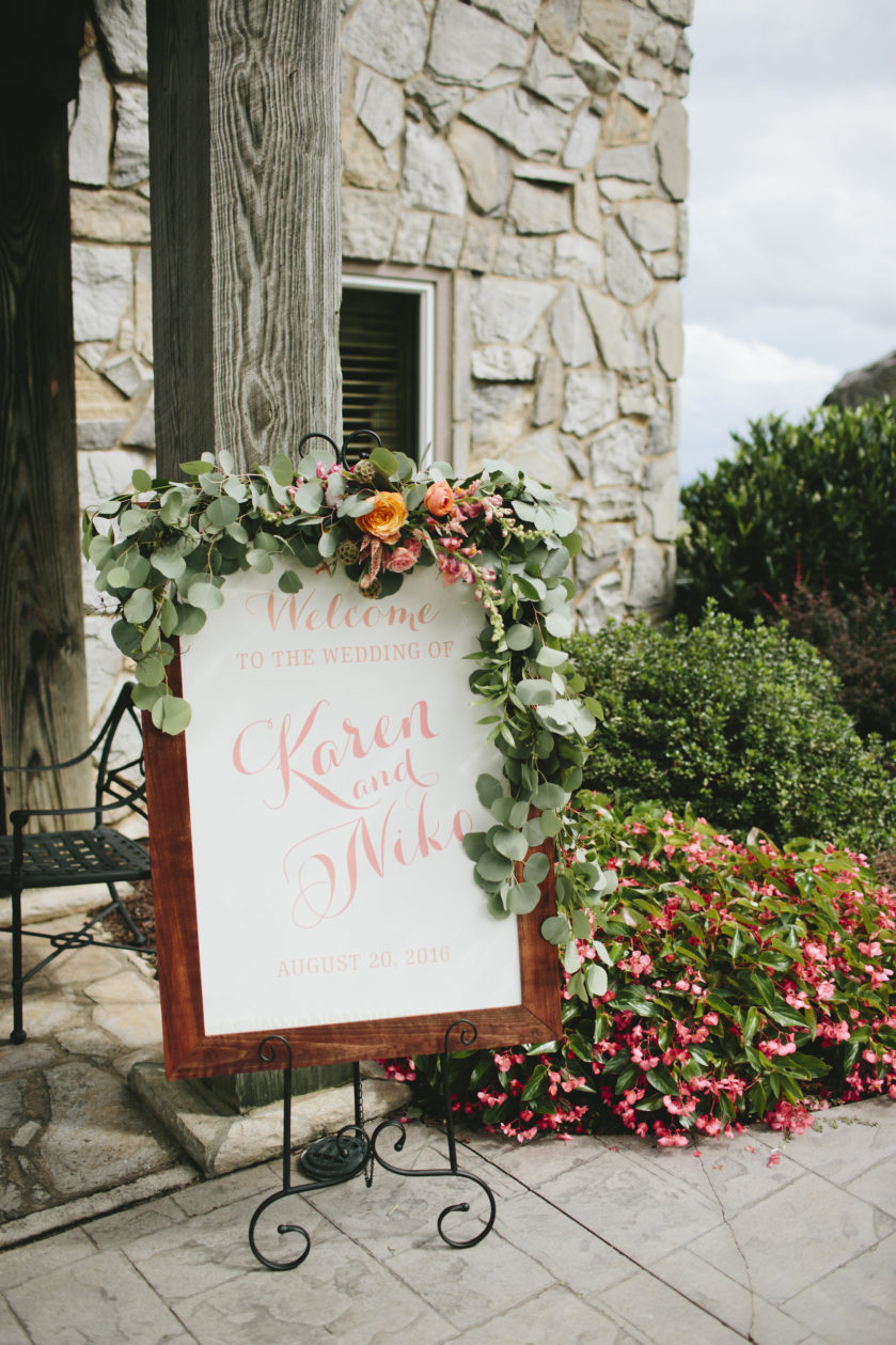 Wedding Welcome Sign, sitting on easel at entryway of a stone chapel