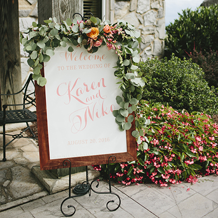 Wedding Ceremony Welcome Sign, Pink and Peach color palette, wooden frame, sitting on easel with greenery and flowers, outside of stone chapel
