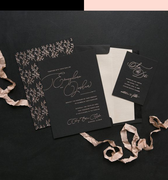 Blush and Black wedding invitation, black card with shiny blush foil wording, formal calligraphy style font and dainty floral details on the back, style on a black background with a silk ribbon