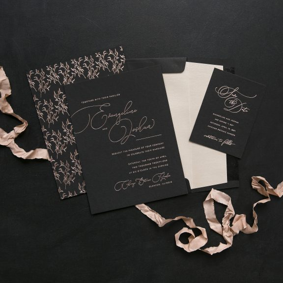 Black and Blush Wedding Invitation, black paper with pink foil, calligraphy style script and whimsical branch illustrations on back of invitation, embellished with a blush ribbon