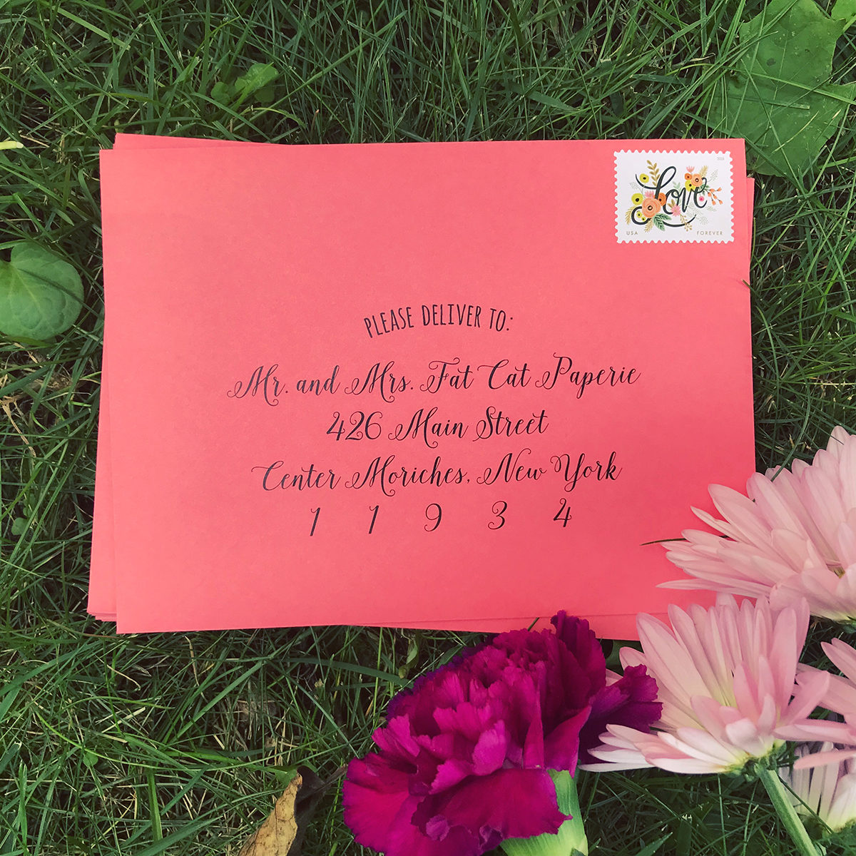 Invitation Guest Addressing, black ink on coral envelope, Rifle Paper love stamps, sitting on grass with flowers