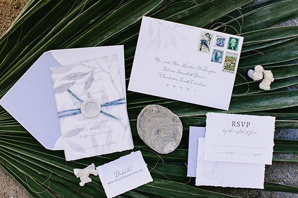 Romantic Wedding Invitation, gray watercolor leaf pattern on vellum overlay, vintage stamps, torn edges, palm fronds and sea shells in the background