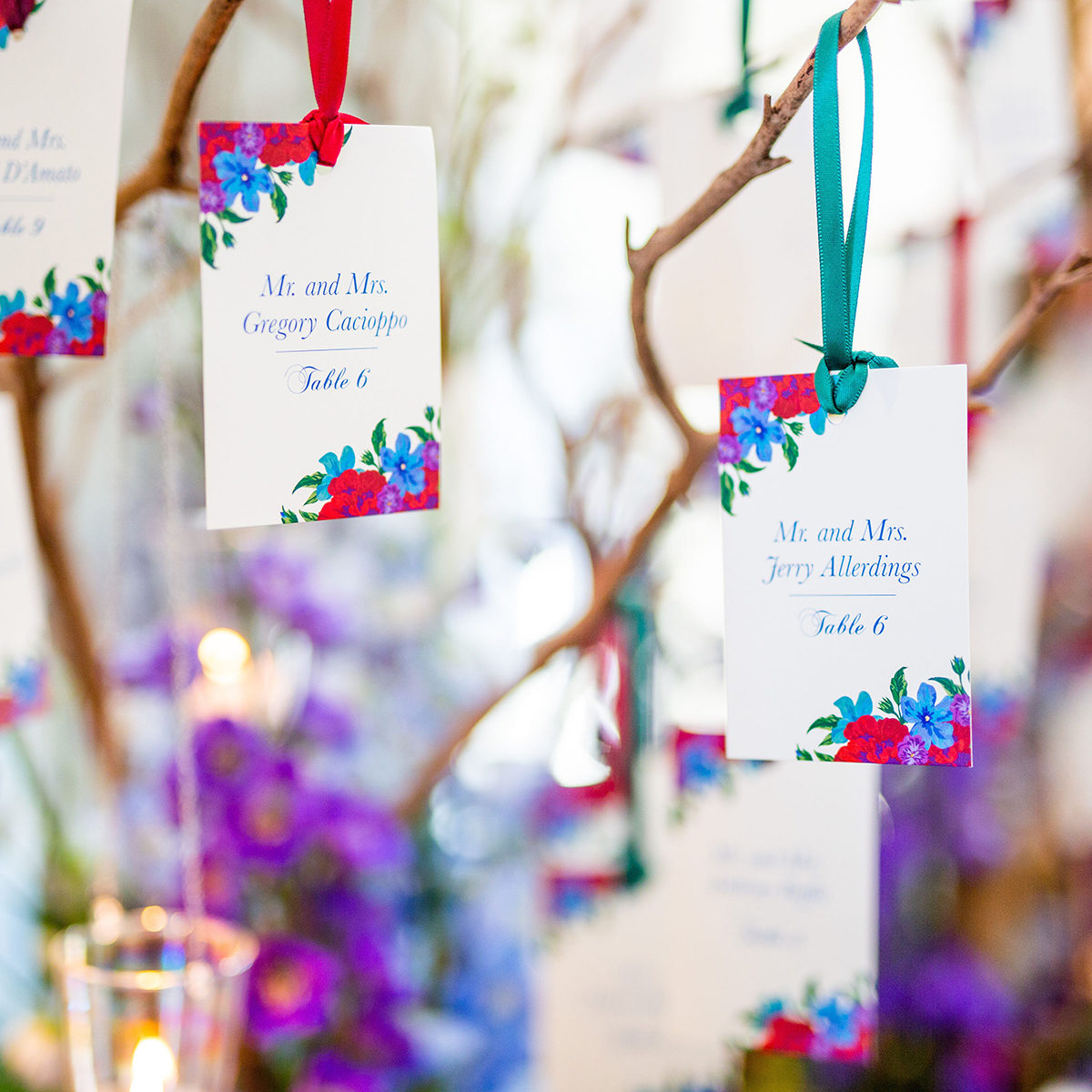 Vibrant jewel tone floral escort cards hanging from a tree branch